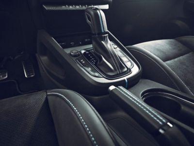 Le pommeau de levier de vitesses et le frein de stationnement gainés de cuir surpiqué dans l'habitacle du Hyundai KONA N.