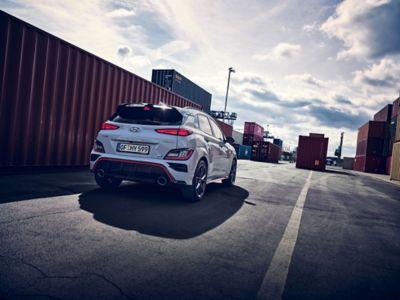 Vue arrière du SUV sportif Hyundai KONA N évoluant à toute vitesse entre les conteneurs d'un site industriel.