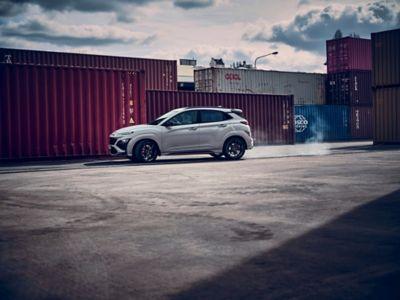 Vue latérale du SUV sportif Hyundai KONA N évoluant à toute vitesse entre les conteneurs d'un site industriel.