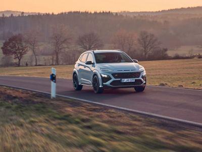 Le SUV sportif Hyundai KONA N évoluant sur une route de campagne au coucher du soleil.