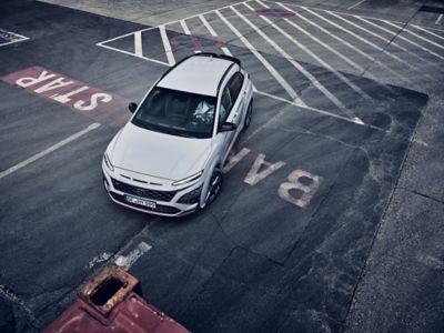 Le SUV sportif Hyundai KONA N dans un environnement industriel, vu de l'avant et légèrement du dessus.