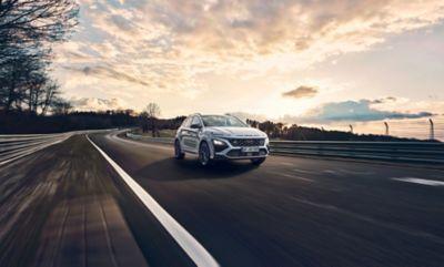 Hyundai KONA N driving on a race track at sunset.