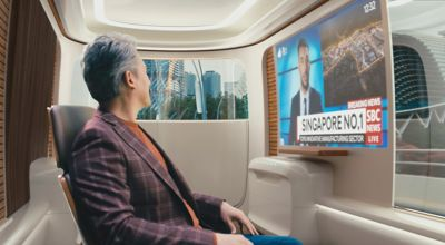 Interior view of a Hyundai future mobility Purpose Built Vehicle with a man watching TV.
