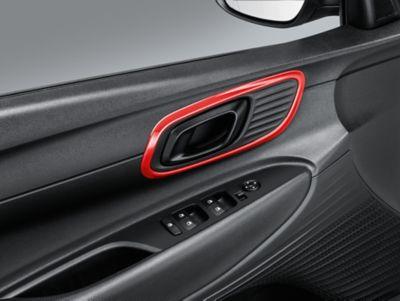 Acabados de los manillares de las puertas en la cabina del Hyundai BAYON en color rojo.