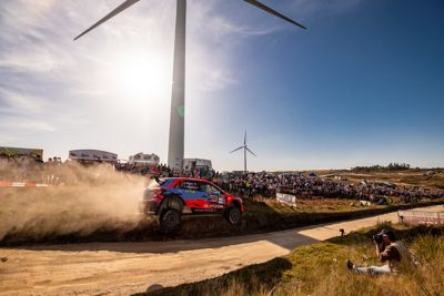 Photo of the Hyundai i20 Coupe WRC racing past a wind turbine.