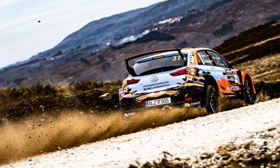 The Hyundai i20 R5, seen from the back, driving across a dust road.