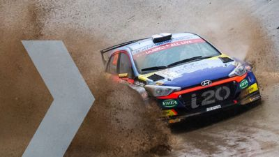 Hyundai Motorsport customer racing rally car i20 R5 in action driving through pudle of mud.
