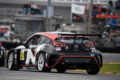 A picture of Hyundai Motorsport's i30 Veloster N TCR in action on a racetrack shown from the rear.