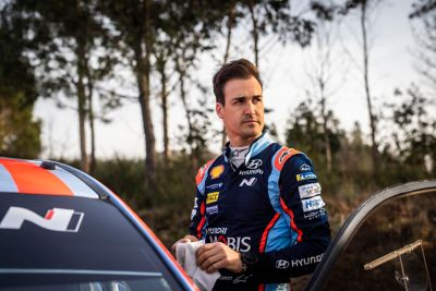 Hyundai Motorsport driver Dani Sardo holding a balaclava standing by the door of his car