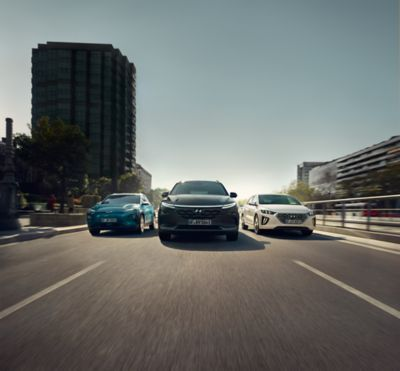 Visual showing the Hyundai  Kona Electric, Nexo and IONIQ Hybrid cars driving down an urban street