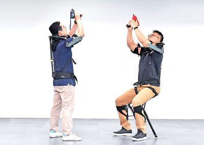 Due uomini provano il giubbotto esoscheletro VEX di Hyundai