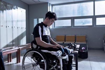 L'atleta paralimpico Jun-beom Park seduto sulla sua sedia a rotelle in uno spogliatoio