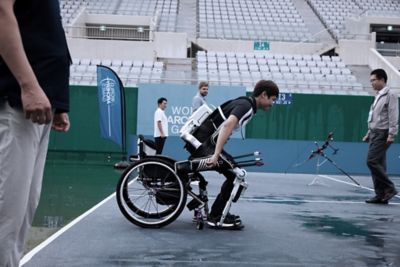 Paralympic athlete Jun-beom Park standing up from his whellchair with Hyundai robotic legs