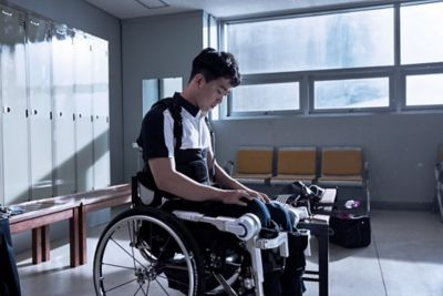Paralympic athlete Jun-beom Park sitting in his wheelchair in a locker room