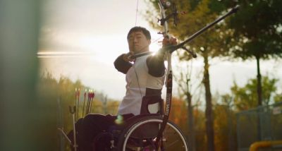 Paralympic athlete Jun-beom Park sitting in his wheelchair practicing archery