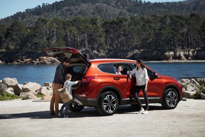 A Hyundai SANTA FE parked next to a lake, a family getting their hiking gear from the opened trunk.