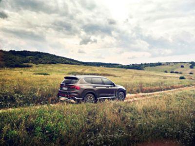 Nuova SANTA FE Plug-in Hybrid, il SUV a 7 posti di Hyundai mentre percorre una strada di campagna in collina