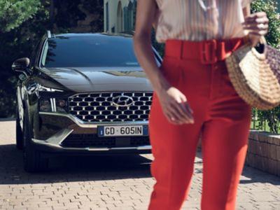 Una donna in piedi davanti a Nuova SANTA FE Plug-in Hybrid, il SUV a 7 posti di Hyundai