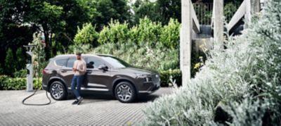 Nuova SANTA FE Plug-in Hybrid, il SUV a 7 posti di Hyundai in fase di ricarica all'esterno di un'abitazione