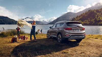 Photo showing the all-new Hyundai Santa Fe in a camping scenario.