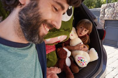 Father standing before his all-new Hyundai Santa Fe's trunk loaded with his daughter and plush animals.