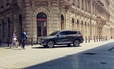 The new Hyundai Santa Fe Plug-in Hybrid 7 seat SUV parked on a city street.