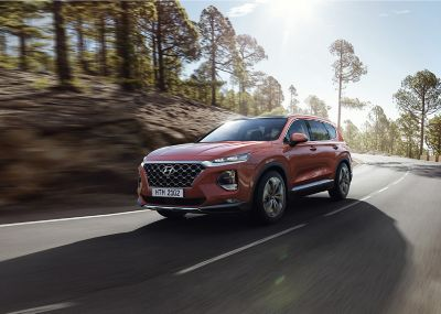 The all-new Hyundai Santa Fe shown driving on a street.