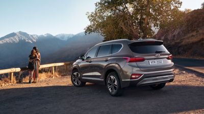 The all-new Hyundai Santa Fe, pictured from the rear, standing before a mountain panorama.