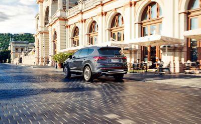 Retro del SUV 7 posti Nuova Hyundai Santa Fe Hybrid durante la guida in città