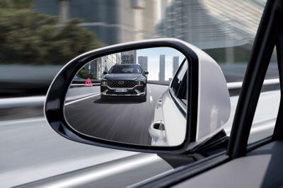 Immagine di una Santa Fe Hybrid nello specchietto retrovisore di un'altro SUV 7 posti Nuova Hyundai Santa Fe Hybrid