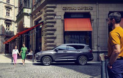 Immagine di Nuova Santa Fe Hybrid parcheggiata davanti a un negozio con donna e bambina che le camminano accanto