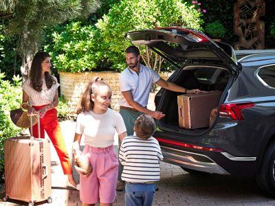 Il SUV 7 posti Nuova Hyundai Santa Fe Hybrid parcheggiato nel cortile di una casa di famiglia.
