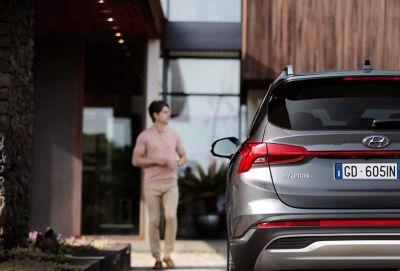 Vista posteriore del SUV 7 posti Nuova Hyundai Santa Fe Hybrid parcheggiato davanti a una casa