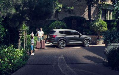 Frontale del SUV 7 posti Nuova Hyundai Santa Fe Hybrid parcheggiato davanti a una casa