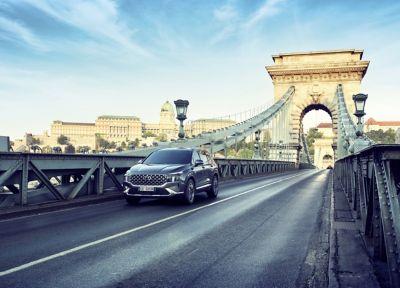 Immagine del SUV 7 posti Nuova Hyundai Santa Fe Hybrid che corre su ponte cittadino