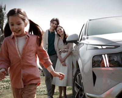 Famiglia in piedi accanto al SUV 7 posti Nuova SANTA FE bianco.