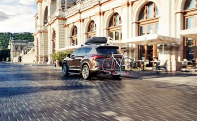 The Hyundai SANTA FE with genuine accessories cross bars, roof box, tow bar and bike carrier.