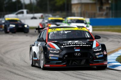 The Hyundai Motorsport's i30 N TCR in action on a racetrack pictured from the front.