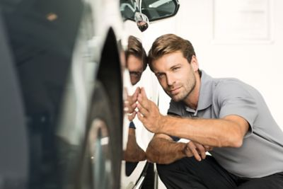 Mann som inspiserer lakken på bil. Foto.