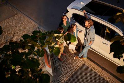 Groupe d'amis se tenant près du Nouveau Hyundai SANTA FE Plug-in.