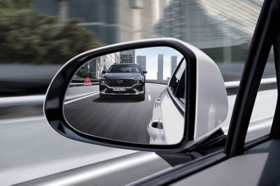 The side mirror of the new Hyundai Santa Fe Hybrid 7 seat SUV reflecting another Santa Fe hybrid.