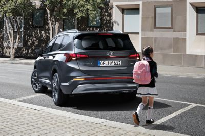 An image of the Reverse Parking Collision-Avoidance Assist on the new Hyundai Santa Fe stopping for a pedestrian.