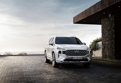 The new Santa Fe 7 seat SUV in white from the front parked in front of a house with ocean view.