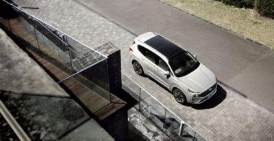 Imagen de la parte superior del nuevo SANTA FE de 7 plazas en color blanco aparcado frente a una casa.