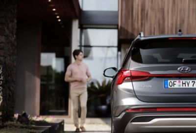 The new Hyundai Santa Fe Hybrid 7 seat SUV from the rear parked in front of a house.