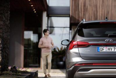 Imagen de la parte trasera del nuevo Hyundai SANTA FE Híbrido de 7 plazas aparcado frente a una casa.