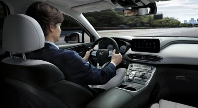 Interior view of the new Hyundai Santa Fe 7 seat SUV with a man driving through a city.