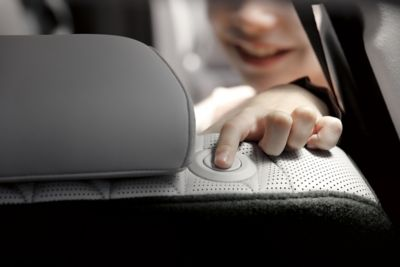 Interior view of the new Hyundai Santa Fe Hybrid 7 seat SUV showing a child adjusting the headrest.