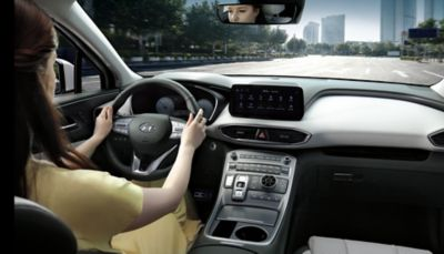 Interior view of the new Hyundai Santa Fe Hybrid 7 seat SUV with a woman driving through a city.