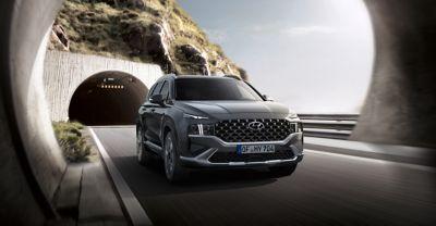 Nowy 7-miejscowy SUV Hyundai SANTA FE Hybrid jadący przez tunel.